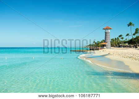 Paradise Caribbean Landscape. Clear Sea, White Sand, Tropical Palm Trees And Lighthouse On Sandy Sho