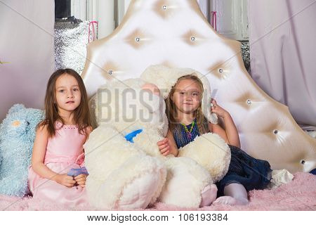 Two little girls in bed with toys