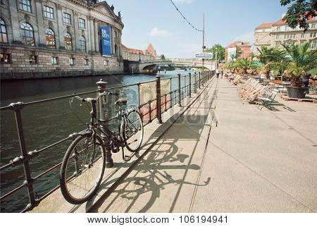 People Relax On Waterfront With Comfortable Chairs And Bicycles
