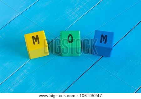 Mom sign on color wooden cubes with light blue wood background.