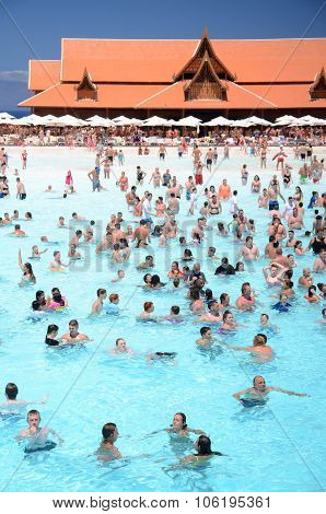 Tourists enjoying artificial wave in Siam Park on Tenerife island,
