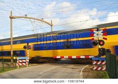 Dutch Train Passing A Railway Crossing