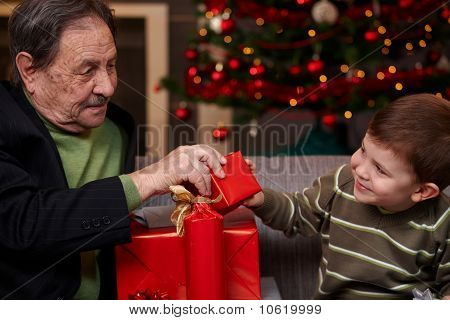 Grandchild Giving Christmas Present To Grandfather