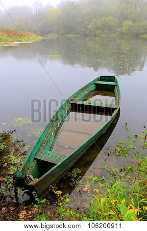 Alone wooden boat on river at the rain time