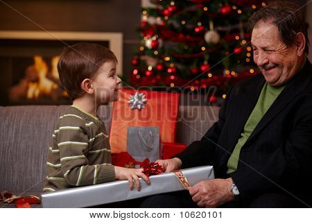 Small Boy Helping Grandfather Wrapping Christmas Gifts