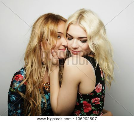 Two girl friends together smiling, studio shot