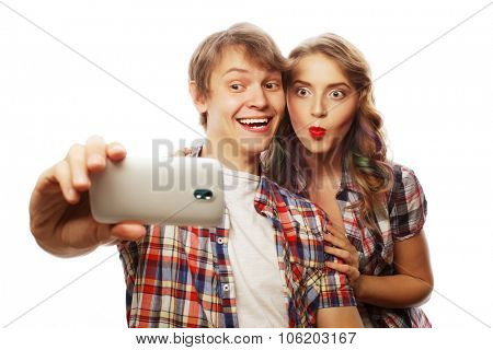 technology, love and friendship concept - smiling couple with smartphone, selfie and fun. Studio shot over white background.