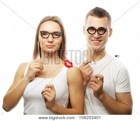 people, party, love and leisure concept - lovely couple holding party glasses and mustaches on sticks, over white  background