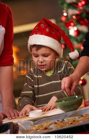 Small Boy In Santa Claus Hat At Christmas Baking