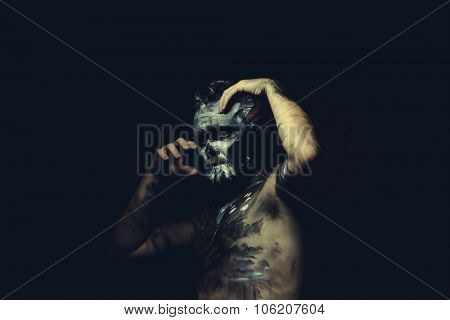 Paint, wild man with white painted face and full body black paint