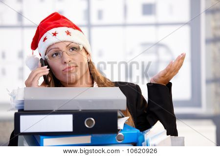 Young Female In Santa Hat Troubled In Office