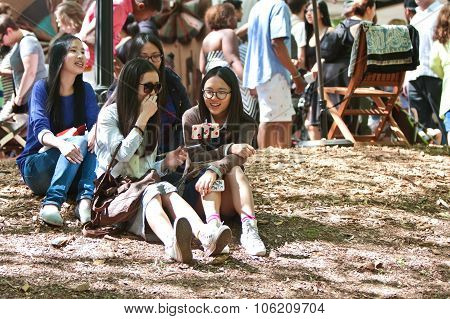 Asian Teenage Girls Laugh While Taking Photo With Selfie Stick