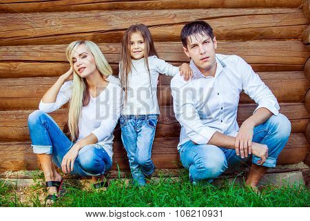 Happy young family sits near the wooden house