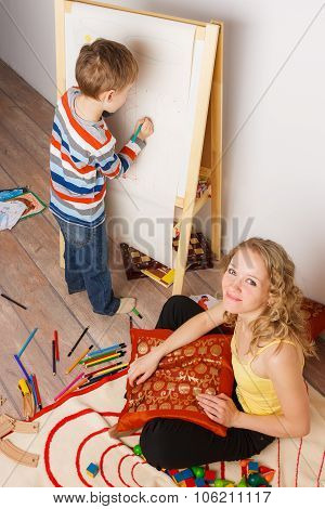Beautiful woman with her child drawing crayons on the easel
