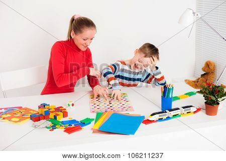 Mother and her son sitting at desk and playing