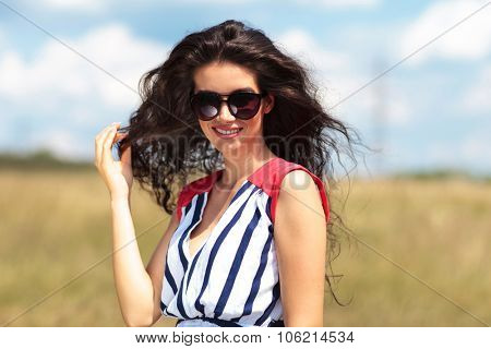 Gorgeous young woman pulling her hair while smiling at the camera.
