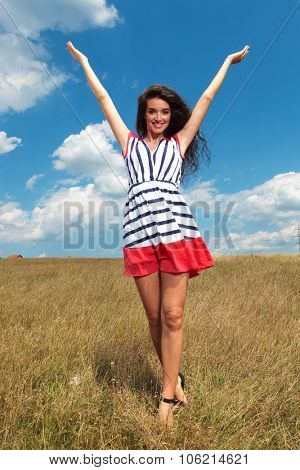 Full body picture of a beautiful woman holding her hand up celebrating freedom.