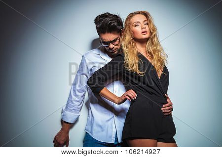 sexy woman touches her waist while her man holds her close and looks down in studio background