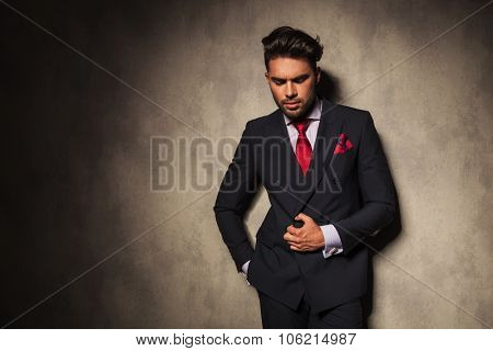 Thoughtful business man looking down while holding his hand in pocket.