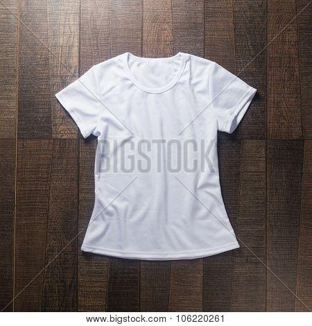 White blank t-shirt on dark wood desk.