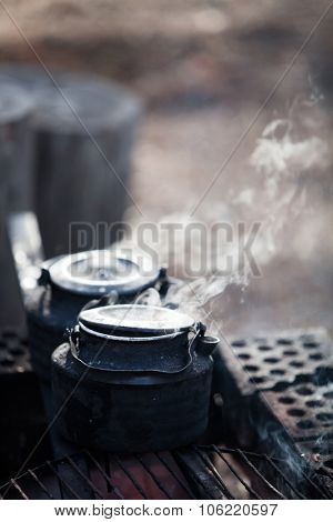 Making coffee by the campfire in forest