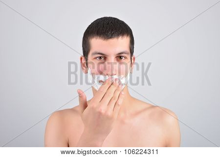 Closeup Of A Young Man Preparing To Shave, He Puts Foam On His Cheek