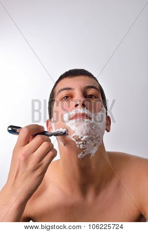 Handsome Young Man With Lots Of Shaving Cream On His Face Is Shaving With Razor
