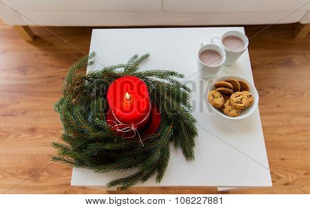 christmas, holidays, winter and still life concept - close up of fir wreath with burning candle, oat cookies and cups with hot chocolate or cocoa drink on table at home