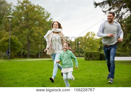 family, parenthood, leisure and people concept - happy mother, father and little girl running and playing catch game in summer park