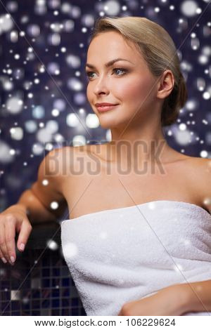 people, beauty, spa, healthy lifestyle and relaxation concept - beautiful young woman sitting in bath towel at sauna with snow effect