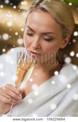 people, beauty, lifestyle, holidays and relaxation concept - beautiful young woman in white bath robe drinking champagne at spa with snow effect