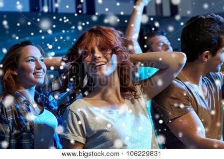 party, holidays, nightlife and people concept - happy friends dancing at night club and snow effect