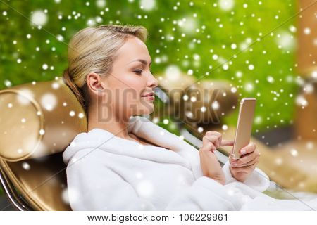 people, beauty, lifestyle, technology and relaxation concept - beautiful young woman in white bath robe with smartphone social networking at spa with snow effect