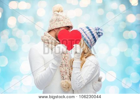 love, valentines day, couple, christmas and people concept - smiling man and woman in winter hats and scarf hiding behind red paper heart shape over blue holidays lights background