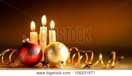 Burning candles in a Christmas setting with seasonal decorations