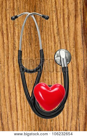 Medical Stethoscope And Red Heart On Wooden Table