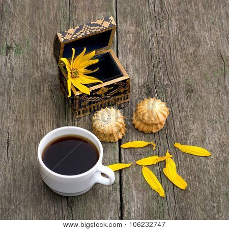 Cup Of Coffee, Open Casket With A Flower, Two Linking Of Cookies And Petals