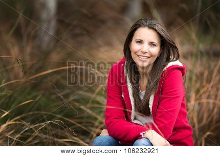 Beautiful smiling woman sitting in brown grass