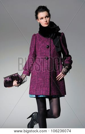 fashion model in autumn/winter clothes with scarf holding handbag posing