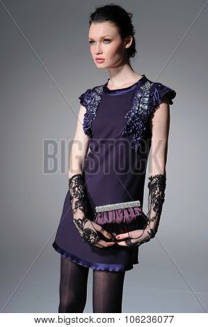 fashion model holding little purse posing on light background