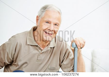 Old smiling senior man with his hand on a cane