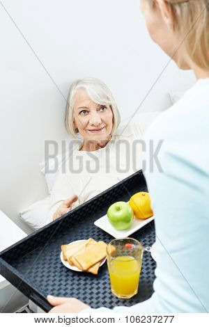Caregiver bringing breakfast to senior woman in bed