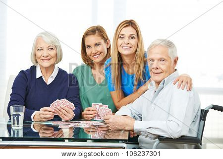 Group of senior people playing cards in nursing home with geriatric nurse