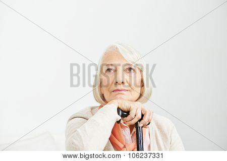 Old woman with cane looking up pensive