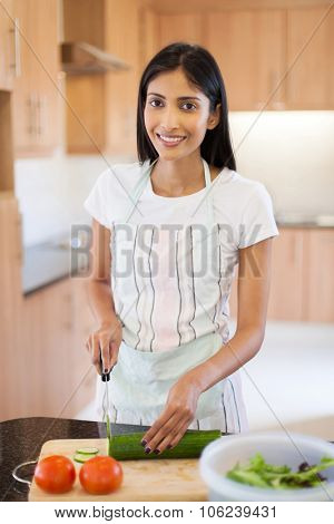 pretty indian woman preparing diner in home kitchen