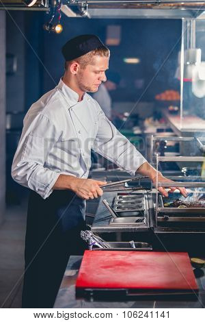 young male cook preparing meal on the grill with metal tongs in hand