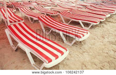 Red sunbeds on sea beach in resort