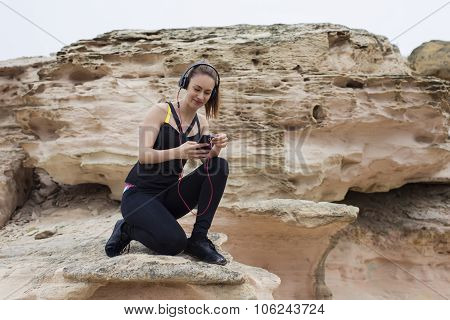 Attractive fitness woman choosing song in play list for listen to music in headphones