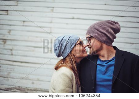 Romantic dates in stylish casualwear touching by their noses