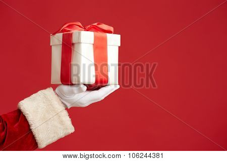 Gloved Santa hand holding giftbox bound with red ribbon